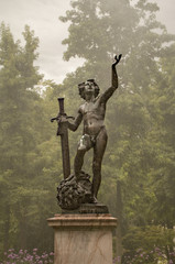 Statue of a naked man in park under rain in Geneva, Swiss