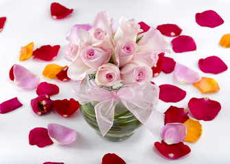 Collection of rose petals with a vase of pink roses in the middl