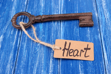 Key to heart, Conceptual photo. On color wooden background