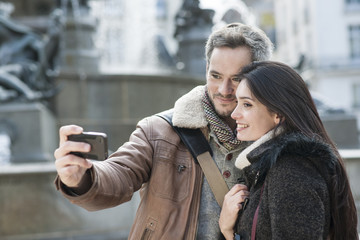 romantic couple in the city taking photo of themselves