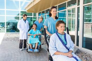 Nurses Assisting Patients On Wheelchairs Outside Hospital Buildi