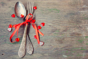 old vintage fork and spoon with red ribbon and hearts