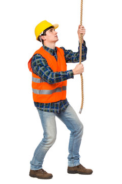 Construction worker pulling a rope.