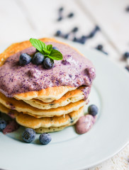 Blueberry pancakes on white wooden background