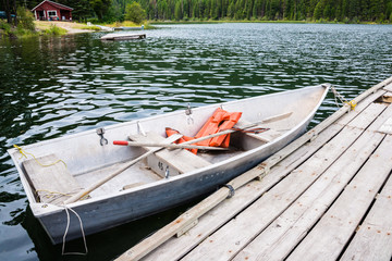 Old Row Boat  with Lifejackets Moored to Dock in Lake