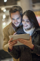 handsome couple using a digital tablet outside with city lights
