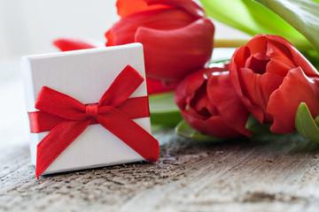 Geschenk und Tulpen auf Holz