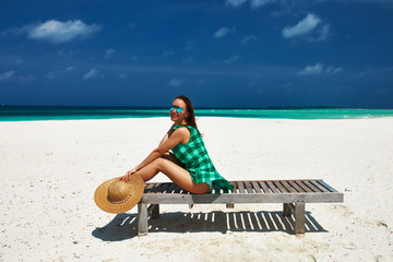 Woman in green dress on a beach at Maldives