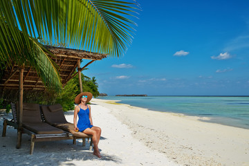 Woman in blue dress on a beach at Maldives