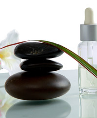 bottles of essential oil and set of stones with flower