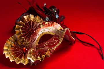 Wall Mural - A red and gold feathered Venetian mask on red background