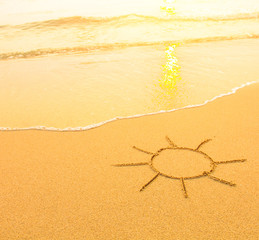 Sun drawn in the sand of a beach, soft surf wave.