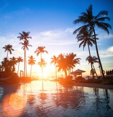 Sunset at a beach luxury resort in tropics.