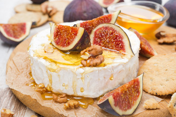 Camembert cheese with honey, figs and crackers on a wooden board