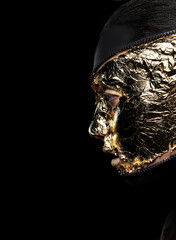 Woman's Face Covered Golden Foil over Black Background. Mystery