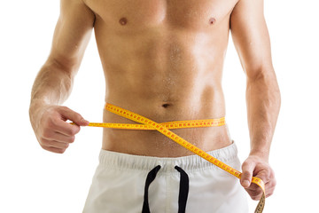 Fit body of shirtless man with tape measure