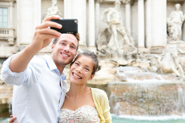 Tourist couple on travel in Rome by Trevi Fountain