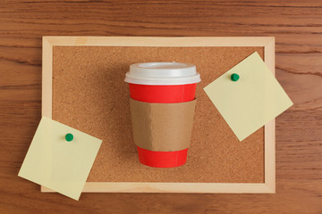 Paper coffee cup and board with notes over wooden background