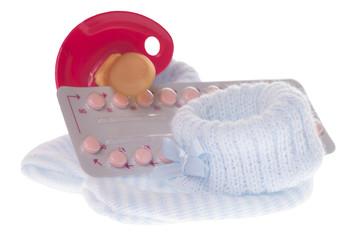 Antibabypille mit Nuckel und Babyschuhen isoliert