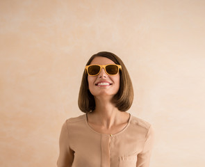 Portrait of beautiful smiling young woman wearing sunglasses