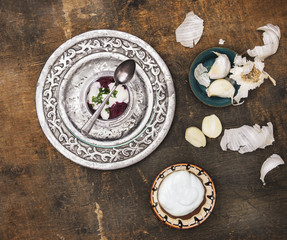 Boiled grated beets with sour cream, silver platter on old wood