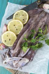 Wall Murals Painterly Inspiration Calamares frescos en la mesa con ingredientes para cocinarlos