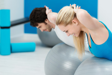 paar im fitness-studio trainiert rückenmuskulatur