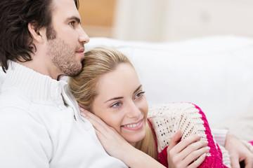 glückliches paar kuschelt auf dem sofa