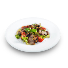 Delicious healthy warm salad with beef and vegetables on a round
