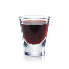Red berries liqueur is the shot glass isolated on white. Bar and