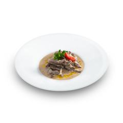 Delicious hot beef stroganoff with cream sauce served on a white