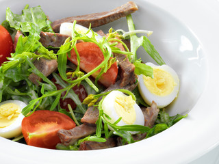 Warm delicious italian salad with beef tongue and arugula on a w