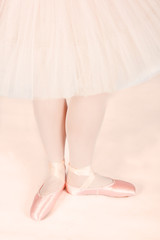 Ballet dancer standing on peach floor while dancing artistic con
