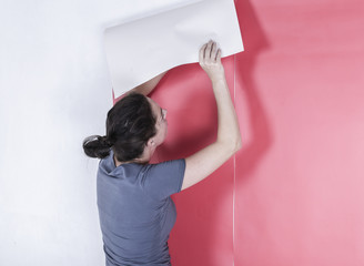 Woman wallpapering the wall. Decorating home interior.