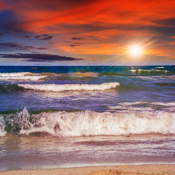 sea waves breaking on the sandy beach at sunset