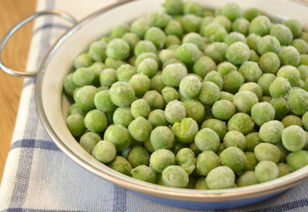Frozen fresh peas in small casserole  on wooden table