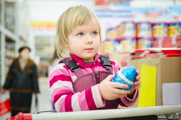 Adorable girl sit on shopping cart with christmas chocolate egg