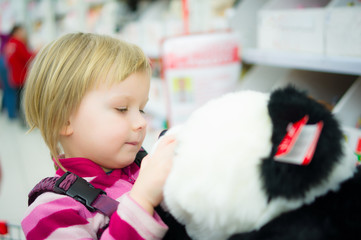 Adorable girl sit on shopping cart with plush panda toys in supe