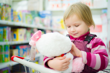 Adorable girl sit on shopping cart with plush kitten toy in supe