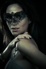 Beautiful young woman in mysterious black Venetian mask. Fashion