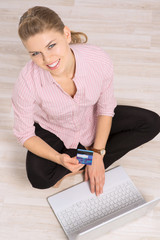 Smiling female shopper sitting with computer and credit card