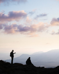 A couple meeting the sunset on the top of the mountain