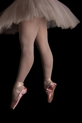 Ballet dancer standing on toes while dancing in pink tutu