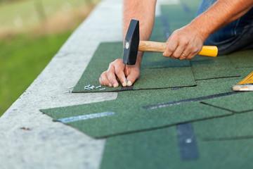 Worker hands installing bitumen roof shingles