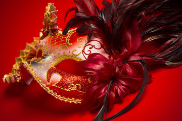 Wall Mural - A red, gold and black mardi gras mask on a red background
