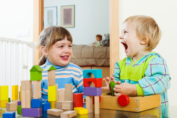 Emotional happy siblings playing with wooden toys