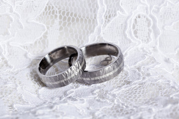 Rustic wedding rings on white lace