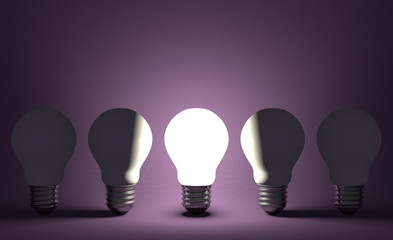 Glowing light bulb in row of switched off ones on violet