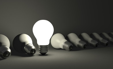 Standing light bulb in row of lying ones on gray