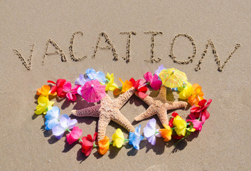 """Sign """"Vacation"""" on the sandy beach with starfishes"""